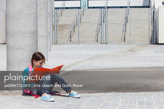Girl reading folder outdoors