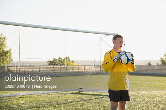 Soccer goalie holding ball in front of net.