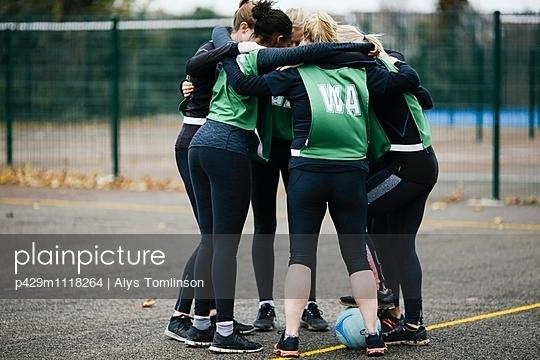 Female netball team in planning huddle on netball court