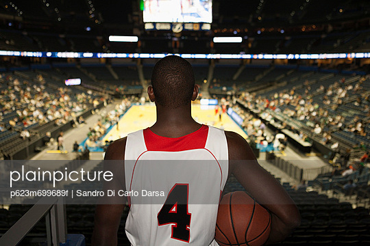Basketball player looking down at stadium, rear view