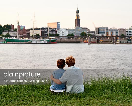 Paar sitzt am Elbufer mit Blick auf den Michel - p1124m1150176 von Willing-Holtz