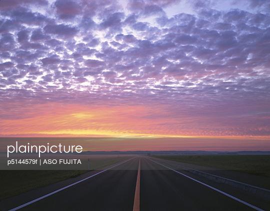 Sunrise over road and fields, Hokkaido, Japan
