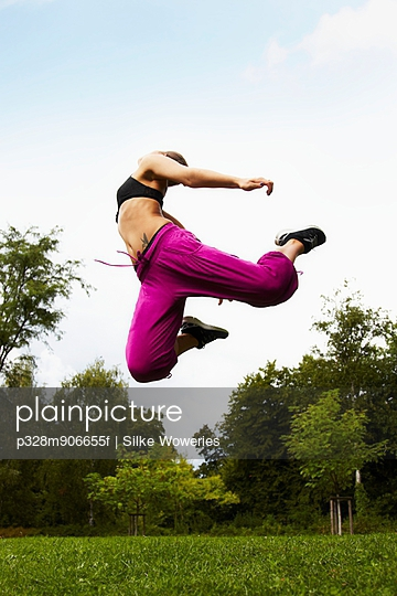 Young adult woman jumping in park