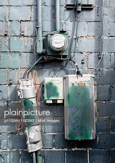 Cable boxes and electric meter on a brick wall in Seattle.
