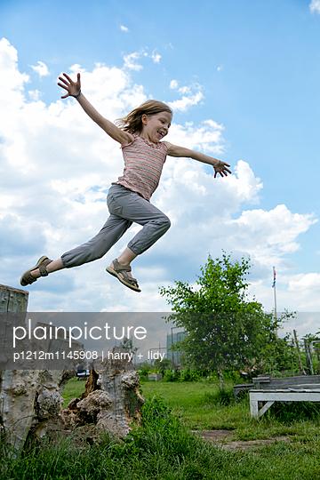 Mädchen springt vom Baumstumpf - p1212m1145908 von harry + lidy