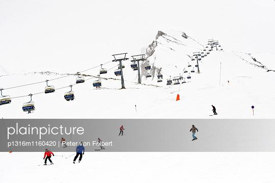Skifahrer auf einer Piste, Sessellift im Hintergrund, Hintertux, Tirol, Österreich - p1316m1160420 von Peter von Felbert