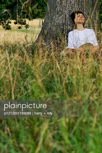 Junge Frau sitzt unter einem Baum - schläft - p1212m1159089 von harry + lidy