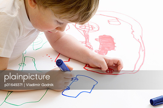 young boy drawing car with felt tip pen