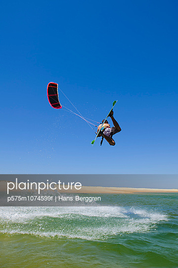 Man kite surfing over sea