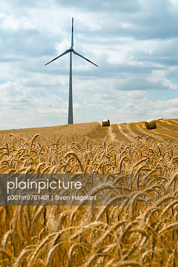 Crops and windmill on field against cloudy sky