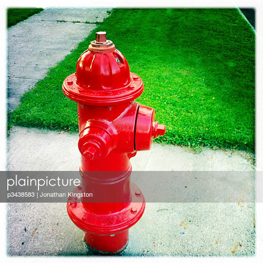 Red fire hydrant, sidewalk and green grass, Bend, Oregon.