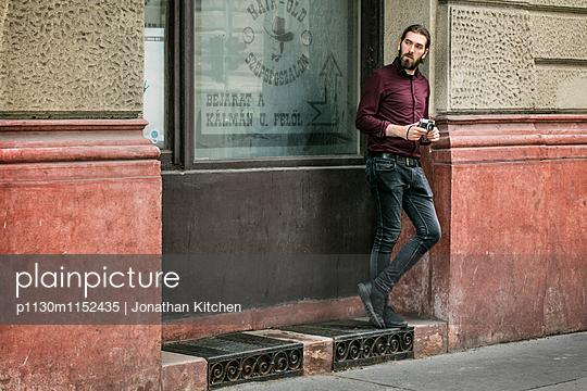 Mann mit Kamera steht vor einem Fenster - p1130m1152435 von Jonathan Kitchen