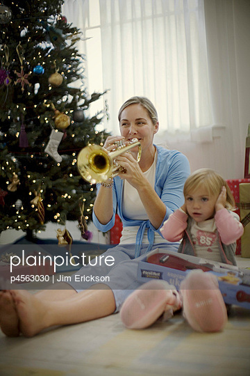 Little girl blocking ears while her mother plays trumpet on Christmas day