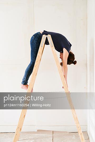 Frau hängt über Leiter - p1124m1160254 von Willing-Holtz