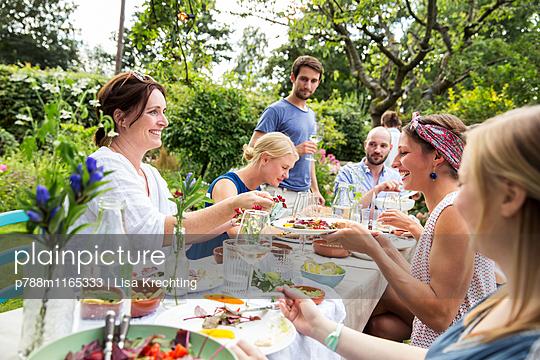 Gemeinsam essen auf einer Gartenparty - p788m1165333 von Lisa Krechting