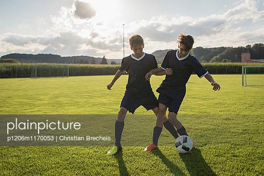 Zwei Jungen spielen Fußball - p1206m1170053 von Christian Brecheis
