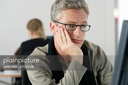 Mature man watching a screen