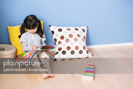 Elementary age girl reading an illustrated book on the floor of the kids room