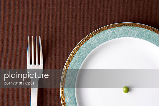 A fork and a single pea on a plate