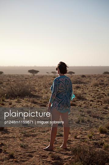 Frau steht in Wüstenlandschaft - p1248m1159871 von miguel sobreira