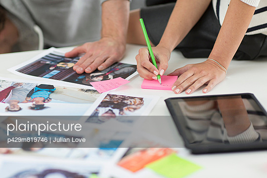 Colleagues making notes on desk of photographs and digital tablet in creative office
