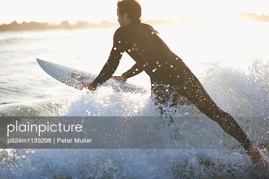 Male surfer surfing into ocean wave on Venice Beach, California, USA