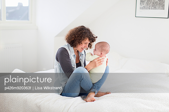 Happy mother playing with baby boy in bed