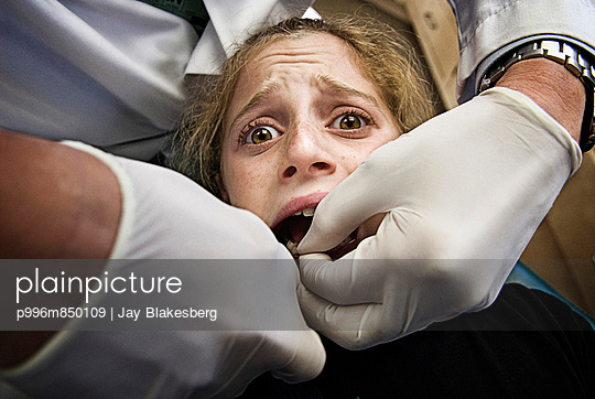 An Orthodontist Removing Braces From A Scared Girl.