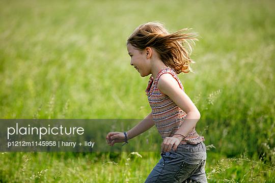 Mädchen springt durch die Wiese - p1212m1145958 von harry + lidy