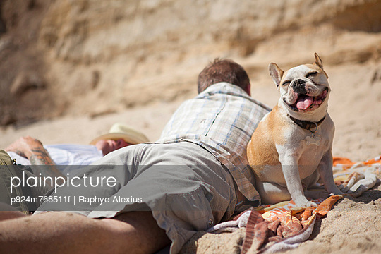Men relaxing with dog on beach