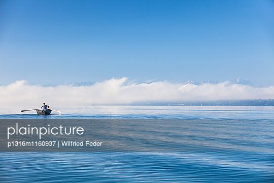 Mann in einem Ruderboot auf dem Starnberger See, Alpen mit Zugspitze im Morgennebel, Berg, Oberbayern, Bayern, Deutschland - p1316m1160937 von Wilfried Feder