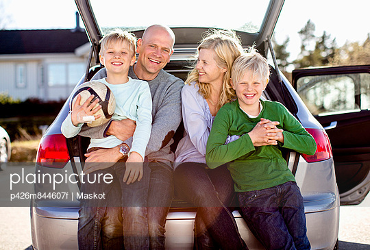 Portrait of happy family sitting on car\'s trunk