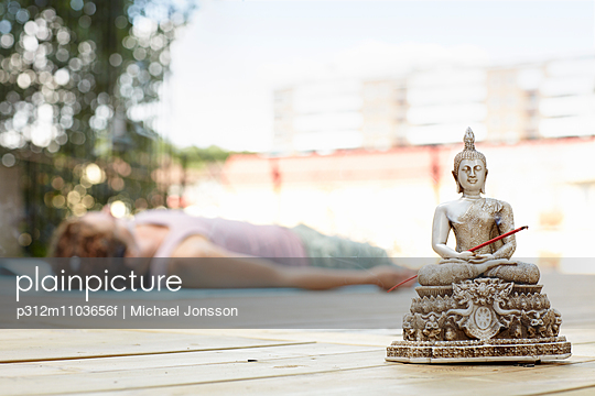Buddha sculpture, woman lying on background