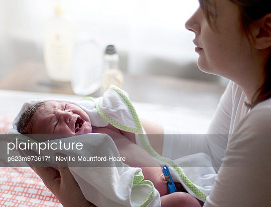 Woman holding crying new born baby