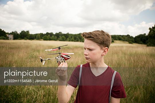 Junge mit Spielzeughubschrauber - p1222m1154545 von Jérome Gerull