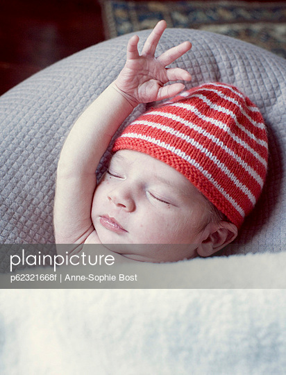 New born baby sleeping with arm raised