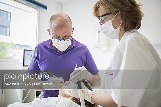 Dentist and dental nurse carrying out dental work on patient
