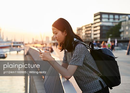 Asiatin mit Smartphone auf Uferpromenade - p1124m1169905 von Willing-Holtz