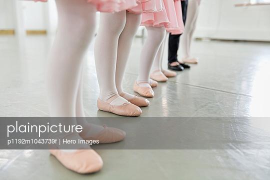 Line of childrens feet in ballet slippers in ballet studio