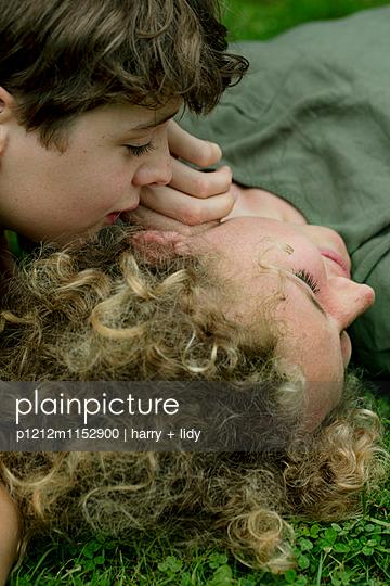 Junge flüstert Mädchen etwas im Ohr - nah - p1212m1152900 von harry + lidy
