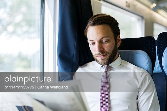 Geschäftsmann liest Zeitung im Zug - p1114m1159775 von Carina Wendland