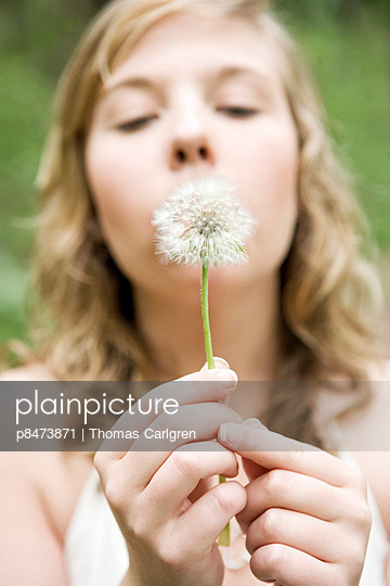 Young Woman Blowing On A Dandelion Ball