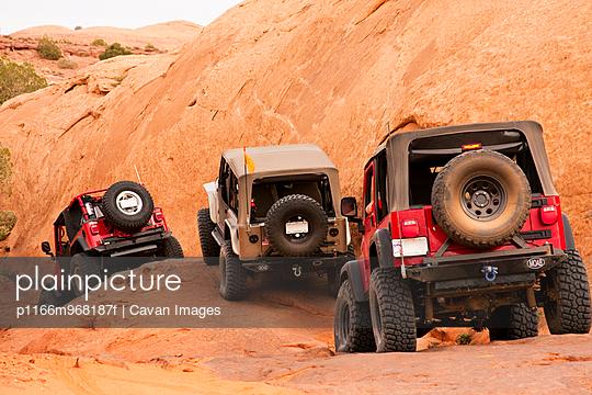 Trucks climbing rocky terrain in Moab, Utah