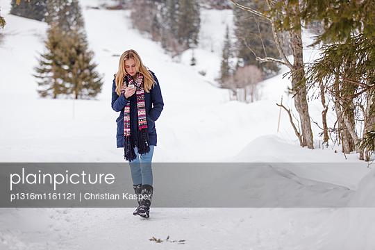 Junge Frau mit einem Handy läuft durch den Schnee, Spitzingsee, Oberbayern, Bayern, Deutschland - p1316m1161121 von Christian Kasper