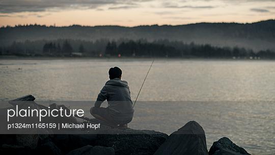 Mann am Seeufer angelt in der Morgendämmerung - p1324m1165159 von michaelhopf