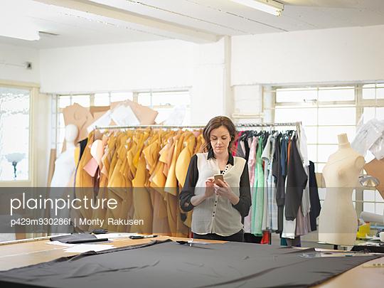 Fashion designer using mobile phone in fashion design studio