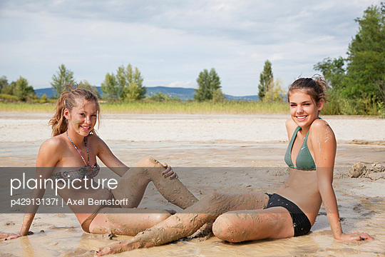 Pretty women lakeside covered in mud