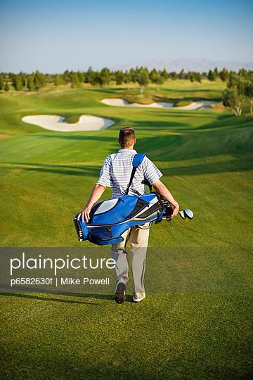 Golfer Carrying Golf Club Bag