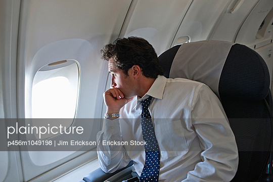 Businessman looking through a window while on an airplane