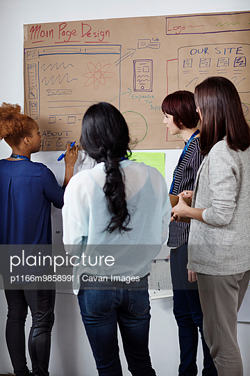 USA, New York State, New York City, Women looking at blueprints in home office